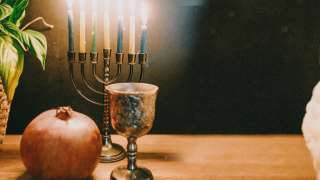 Lighting the candles of a candelabrum with nine branches during Hanukkah festival